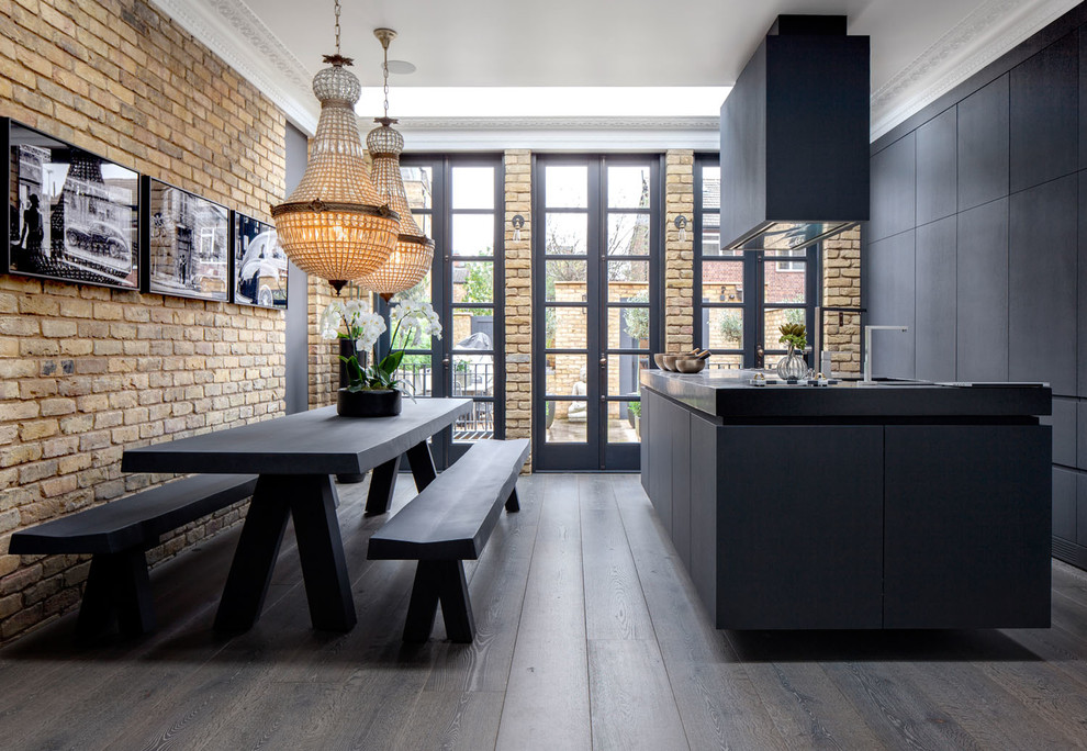 Example of a mid-sized urban galley dark wood floor and brown floor eat-in kitchen design in London with flat-panel cabinets, black cabinets, concrete countertops, paneled appliances and an island