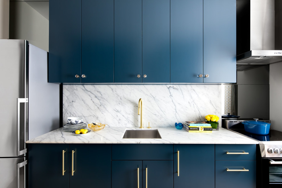 Trendy single-wall kitchen photo in Toronto with an undermount sink, flat-panel cabinets, blue cabinets, white backsplash, stainless steel appliances, no island and stone slab backsplash