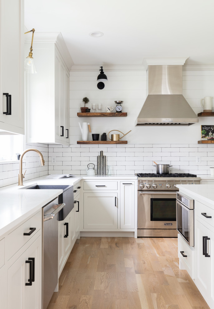 Example of a huge country light wood floor and brown floor open concept kitchen design in New York with a farmhouse sink, white cabinets, white backsplash, ceramic backsplash, stainless steel appliances, an island, white countertops and shaker cabinets