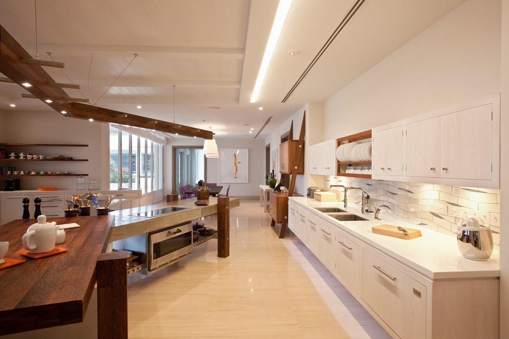 Large trendy travertine floor kitchen photo in Other with an undermount sink, ceramic backsplash, an island, flat-panel cabinets, light wood cabinets and white backsplash