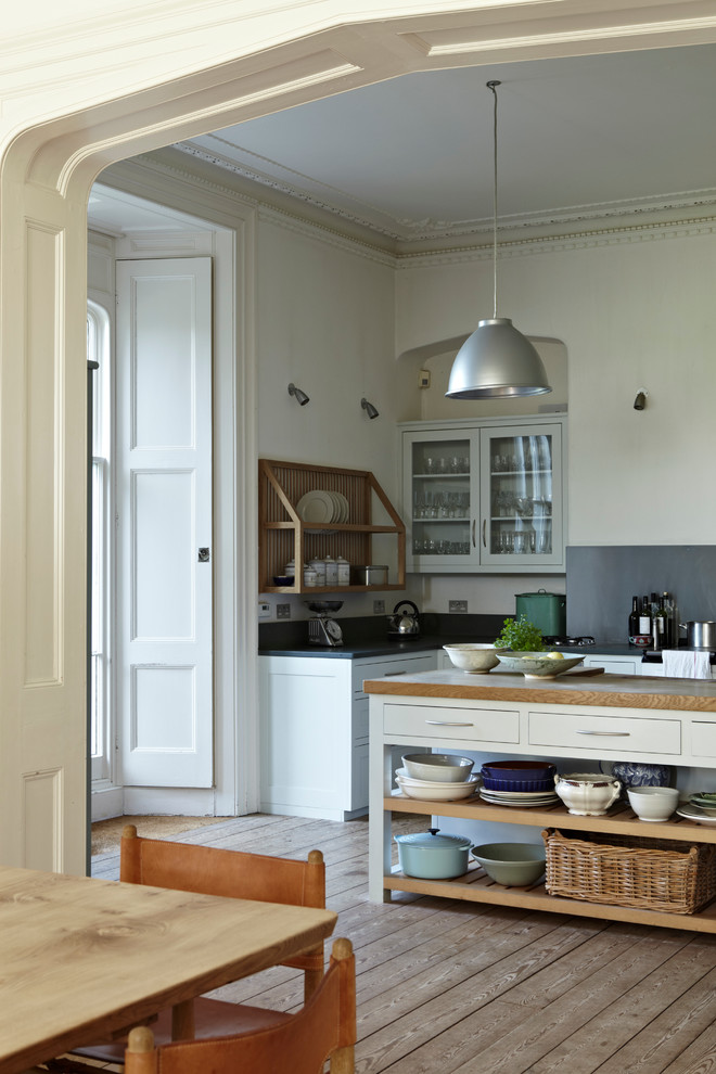 Example of a large farmhouse galley light wood floor eat-in kitchen design in Dorset with flat-panel cabinets, beige cabinets, wood countertops, blue backsplash, stainless steel appliances and an island