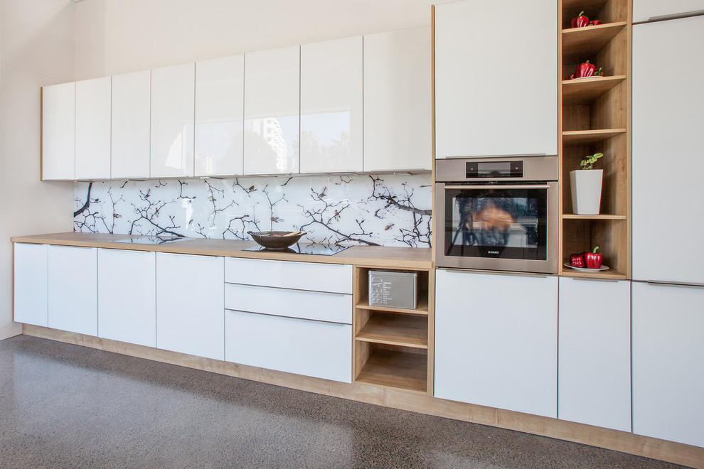 Inspiration for a mid-sized scandinavian galley kitchen in Auckland with wood benchtops, white splashback, glass sheet splashback, stainless steel appliances and travertine floors.