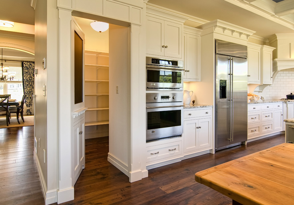 Example of a classic kitchen design in Other with stainless steel appliances and subway tile backsplash