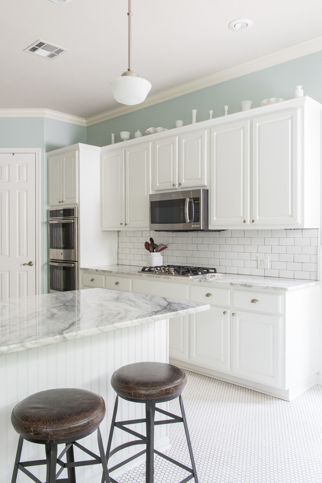 Mid-sized country l-shaped porcelain tile eat-in kitchen photo in Austin with an undermount sink, raised-panel cabinets, white cabinets, quartzite countertops, white backsplash, subway tile backsplash, stainless steel appliances and a peninsula