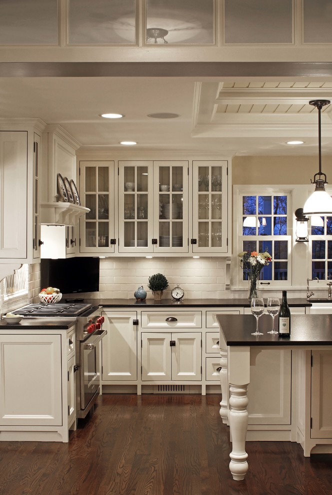 Elegant l-shaped dark wood floor kitchen photo in Omaha with a farmhouse sink, recessed-panel cabinets, white cabinets, white backsplash, subway tile backsplash, stainless steel appliances and an island