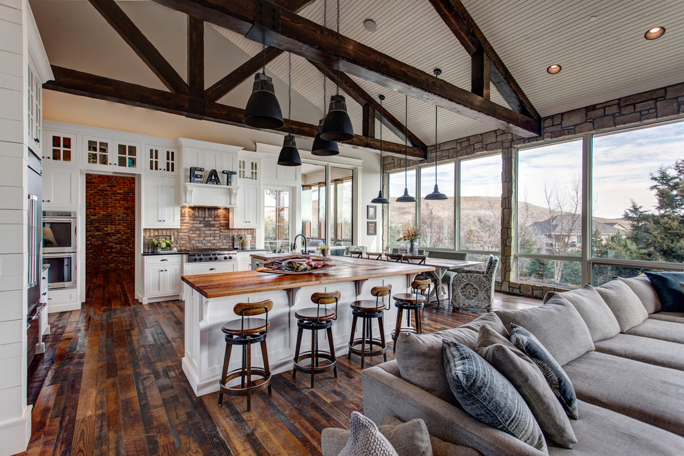 Farmhouse u-shaped dark wood floor and brown floor open concept kitchen photo in Other with shaker cabinets, white cabinets, stainless steel appliances and an island