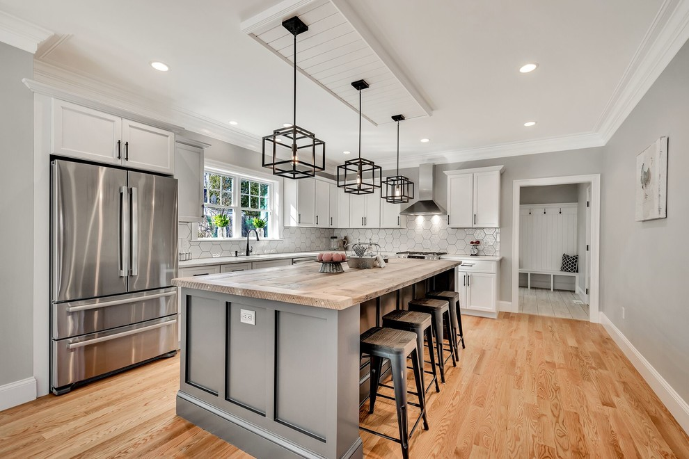 Example of a cottage l-shaped medium tone wood floor and brown floor kitchen design in Boston with shaker cabinets, white cabinets, wood countertops, white backsplash, stainless steel appliances, an island and beige countertops