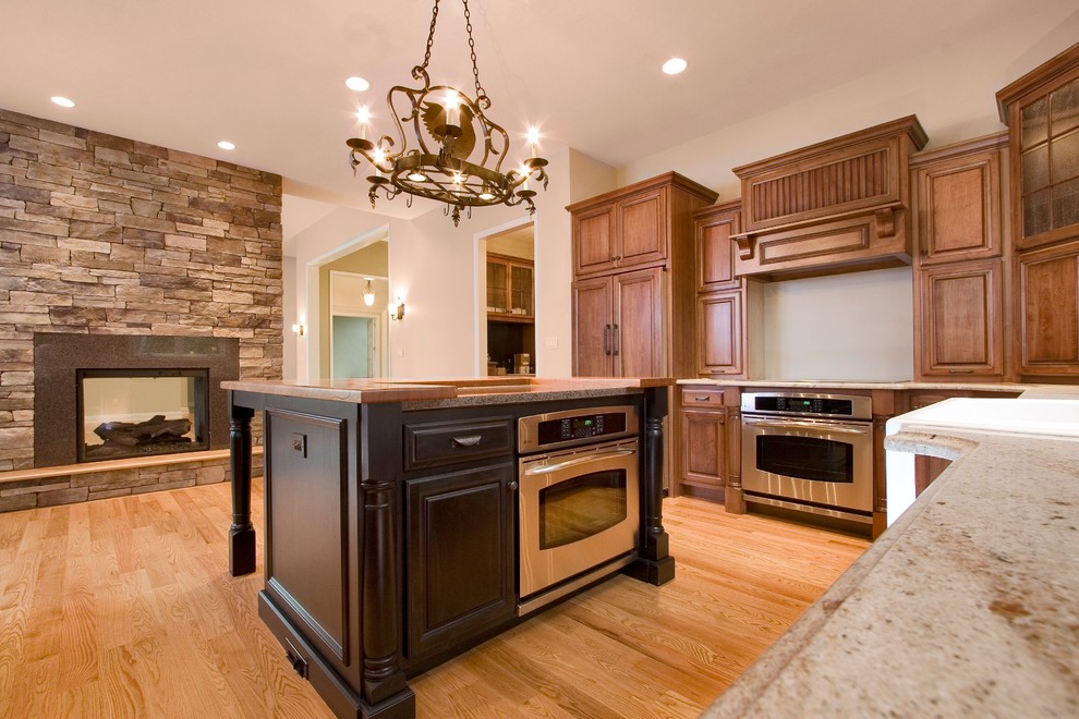 Open concept kitchen - mid-sized transitional l-shaped light wood floor open concept kitchen idea in Other with raised-panel cabinets, medium tone wood cabinets, granite countertops, stainless steel appliances and an island