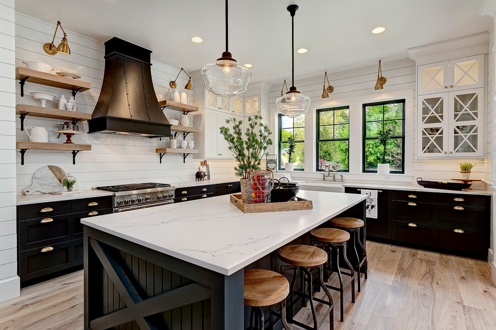 Example of a farmhouse l-shaped medium tone wood floor and brown floor kitchen design in Los Angeles with quartz countertops, a farmhouse sink, shaker cabinets, black cabinets, stainless steel appliances and an island