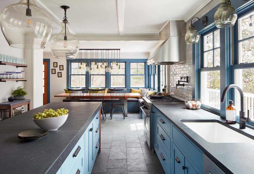 Eat-in kitchen - mid-sized country slate floor and gray floor eat-in kitchen idea in Boston with a single-bowl sink, blue cabinets, limestone countertops, white backsplash, subway tile backsplash, stainless steel appliances and an island