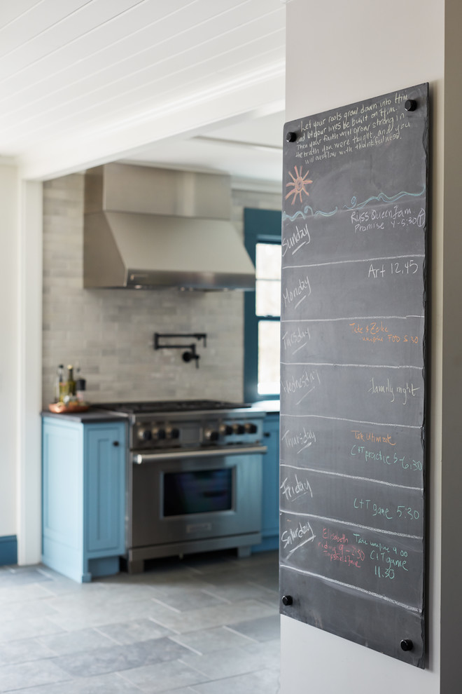 Mid-sized farmhouse single-wall slate floor and gray floor eat-in kitchen photo in Boston with recessed-panel cabinets, blue cabinets, limestone countertops, gray backsplash, stainless steel appliances and an island