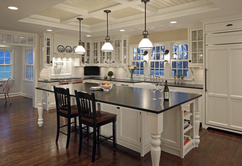 Country kitchen photo in Omaha with glass-front cabinets, white backsplash, subway tile backsplash, paneled appliances, white cabinets and granite countertops