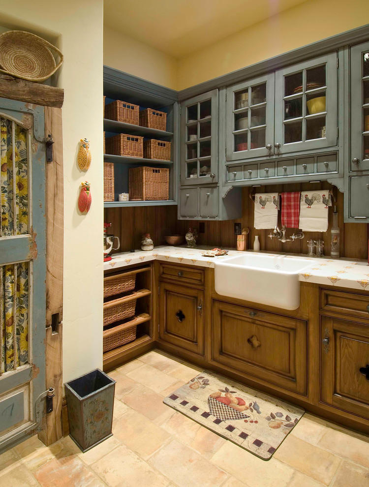Example of a cottage kitchen design in Denver with a farmhouse sink, glass-front cabinets and blue cabinets