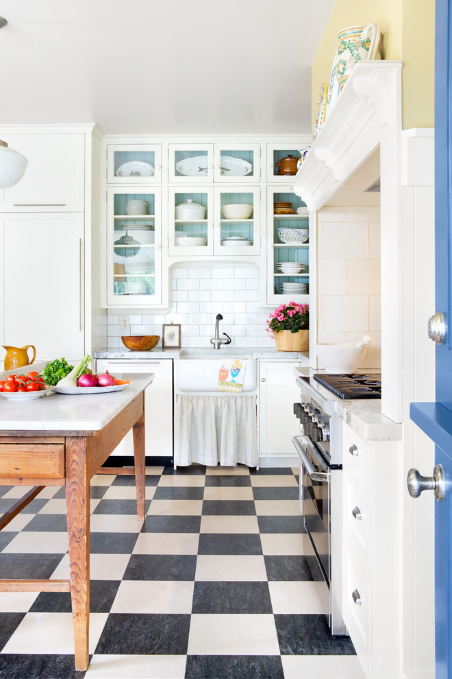 Kitchen - country l-shaped kitchen idea in Minneapolis with a farmhouse sink, glass-front cabinets, white cabinets, marble countertops, white backsplash, subway tile backsplash, paneled appliances and an island