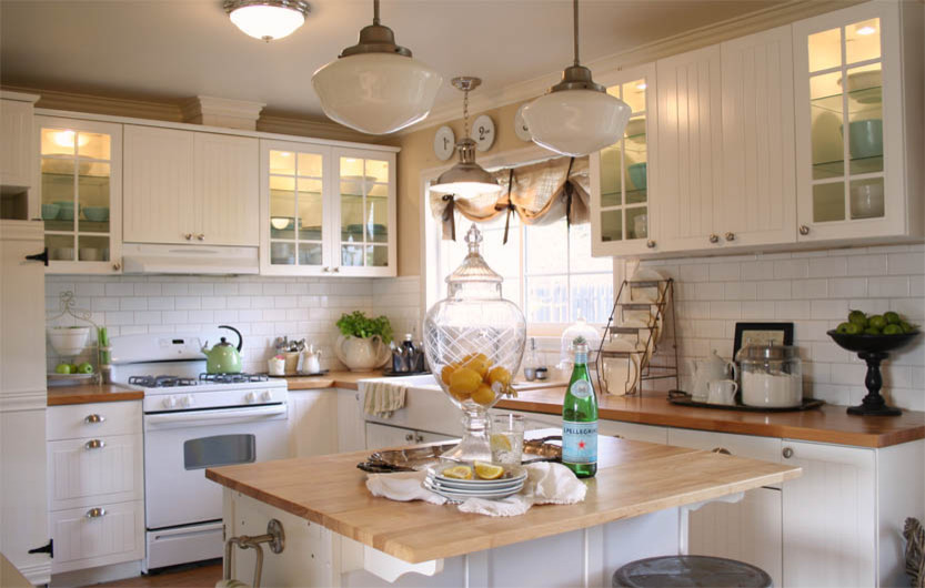 Eat-in kitchen - mid-sized traditional l-shaped vinyl floor eat-in kitchen idea in Los Angeles with a farmhouse sink, glass-front cabinets, white cabinets, wood countertops, white backsplash, subway tile backsplash, white appliances and an island