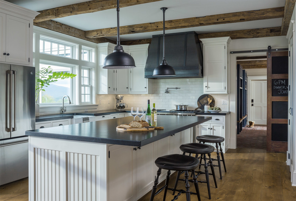 Mid-sized cottage u-shaped medium tone wood floor and brown floor kitchen photo in Other with a farmhouse sink, white cabinets, granite countertops, white backsplash, subway tile backsplash, stainless steel appliances, an island, black countertops and beaded inset cabinets