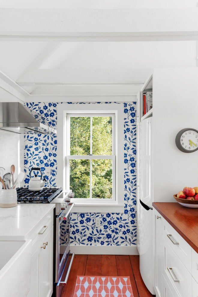 Inspiration for a small farmhouse galley medium tone wood floor kitchen remodel in Boston with a farmhouse sink, white cabinets, quartzite countertops, white backsplash, stainless steel appliances, white countertops and shaker cabinets