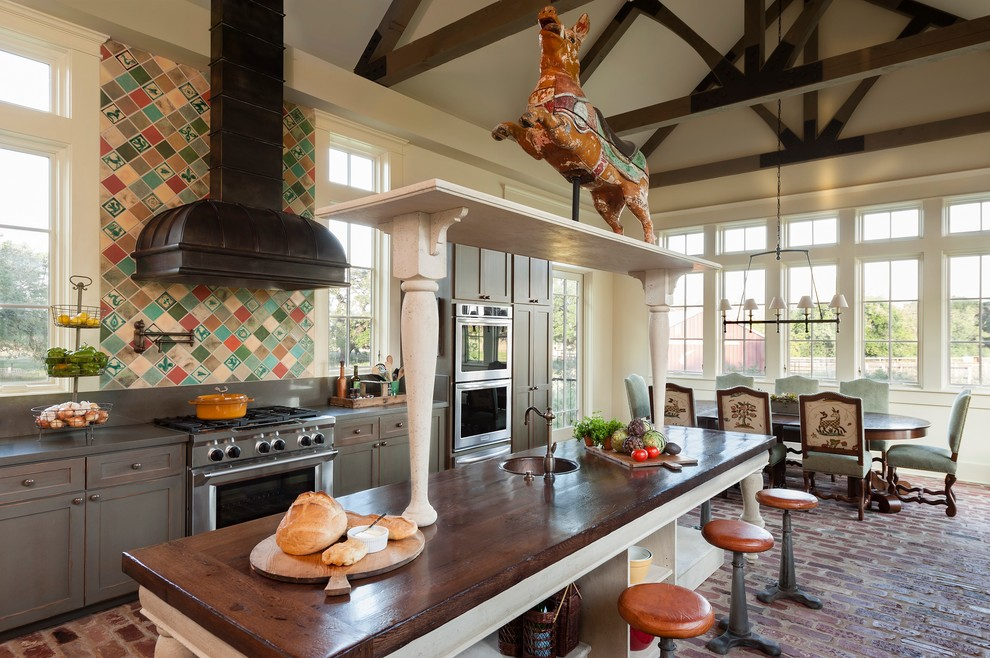 Example of a cottage brick floor eat-in kitchen design in Houston with shaker cabinets, gray cabinets, multicolored backsplash, stainless steel appliances and an island
