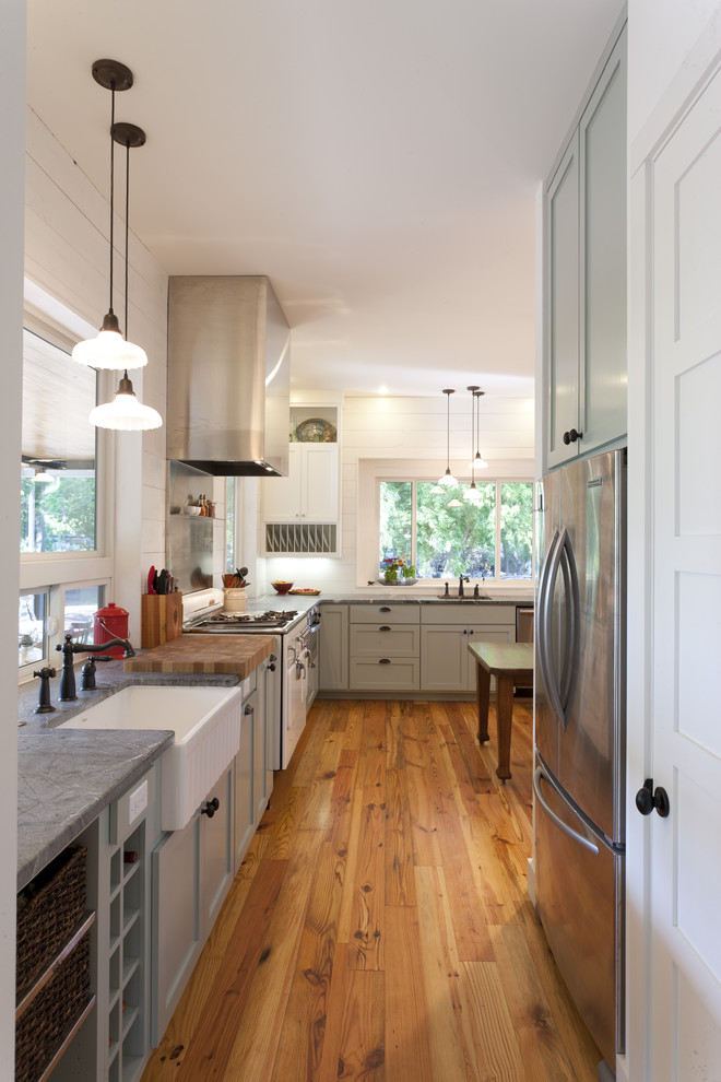 Kitchen - farmhouse kitchen idea in Austin with stainless steel appliances, a farmhouse sink and soapstone countertops