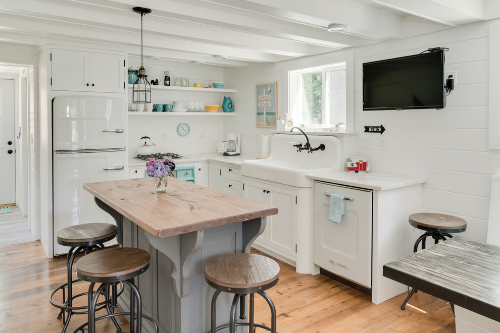Example of a beach style l-shaped light wood floor kitchen design in Grand Rapids with shaker cabinets, white cabinets, wood countertops, white appliances and an island