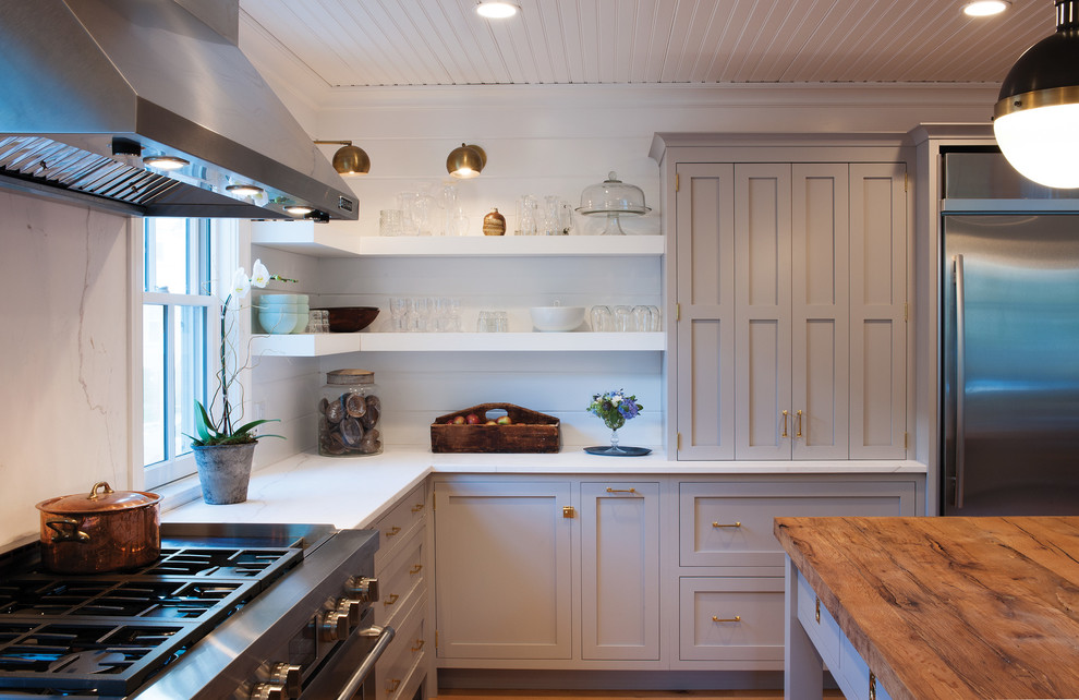Kitchen - cottage u-shaped light wood floor kitchen idea in Boston with flat-panel cabinets, gray cabinets, white backsplash, stainless steel appliances and an island