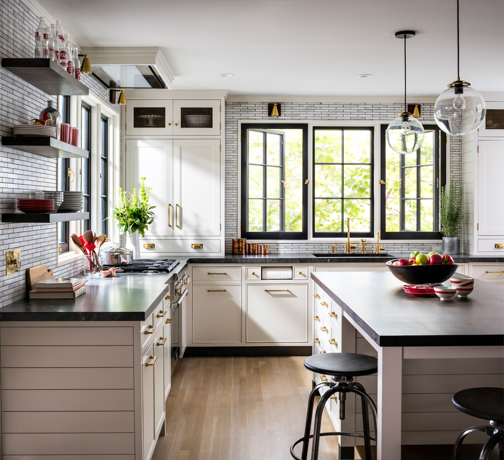 This is an example of a mid-sized country u-shaped open plan kitchen in New York with an undermount sink, shaker cabinets, grey cabinets, granite benchtops, grey splashback, mosaic tile splashback, coloured appliances, light hardwood floors, an island and brown floor.