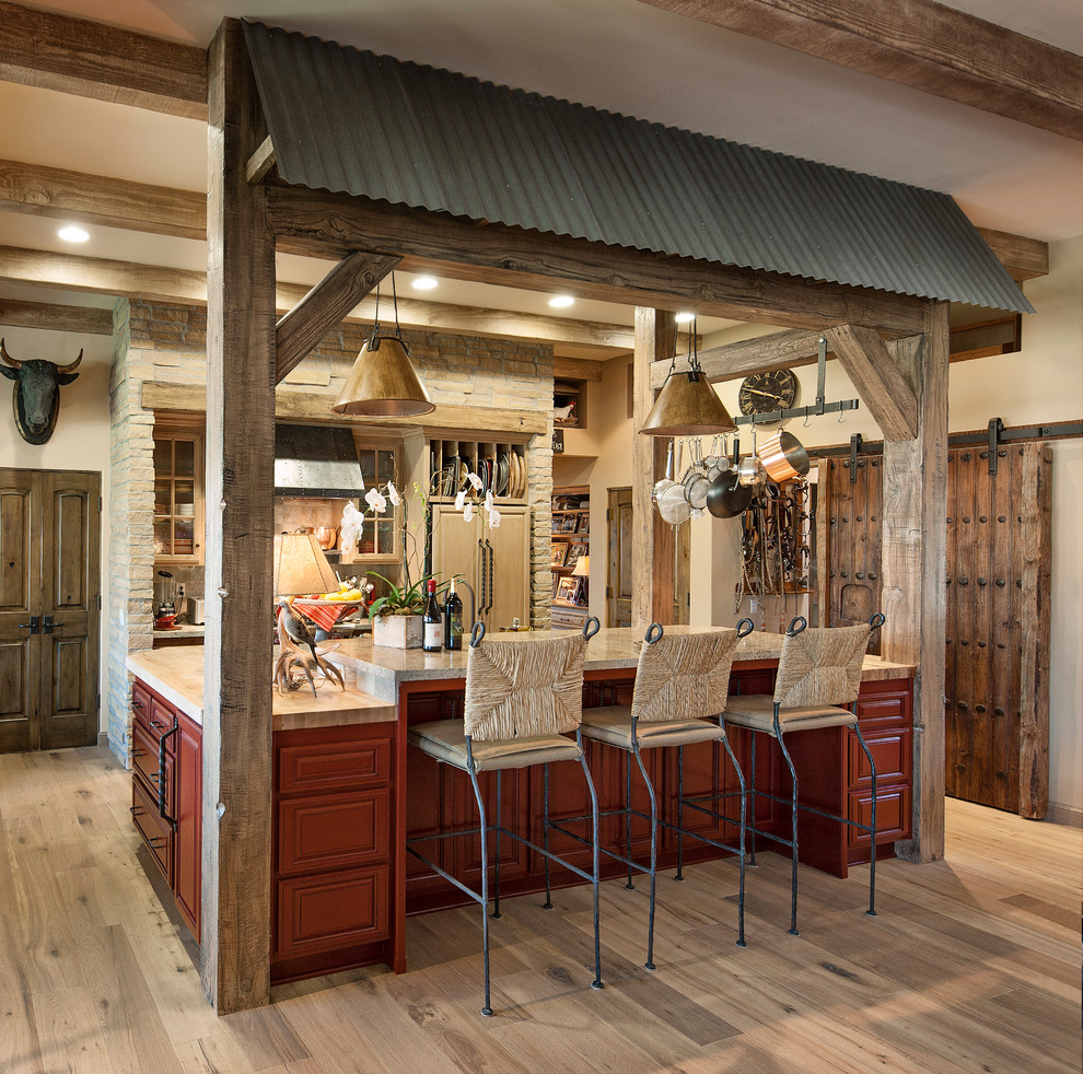 Inspiration for a mid-sized southwestern galley medium tone wood floor kitchen remodel in Santa Barbara with beaded inset cabinets, stone tile backsplash, paneled appliances, an island and medium tone wood cabinets
