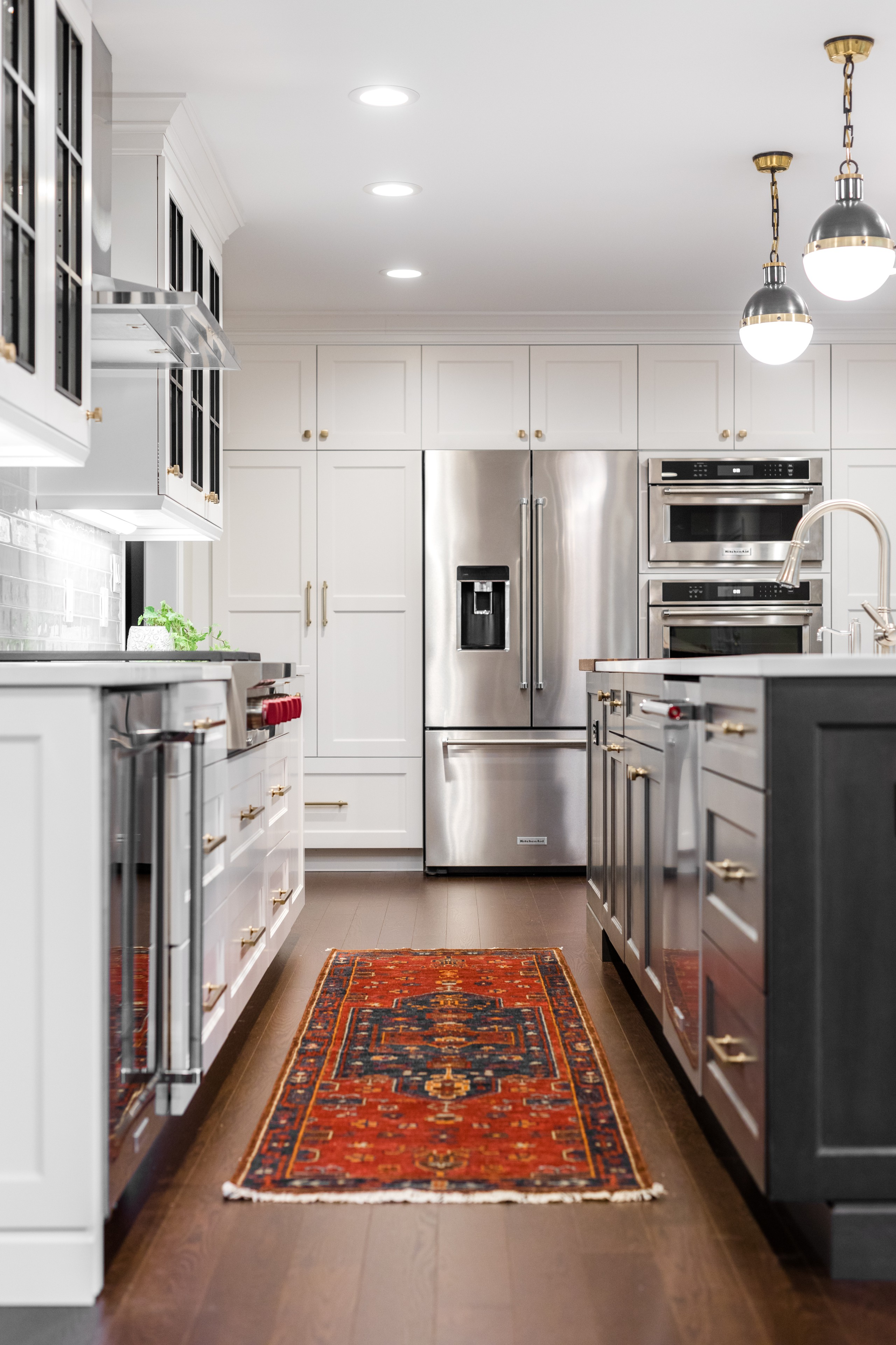 Example of a country galley medium tone wood floor and brown floor eat-in kitchen design in Detroit with shaker cabinets, medium tone wood cabinets, quartz countertops, gray backsplash, ceramic backsp