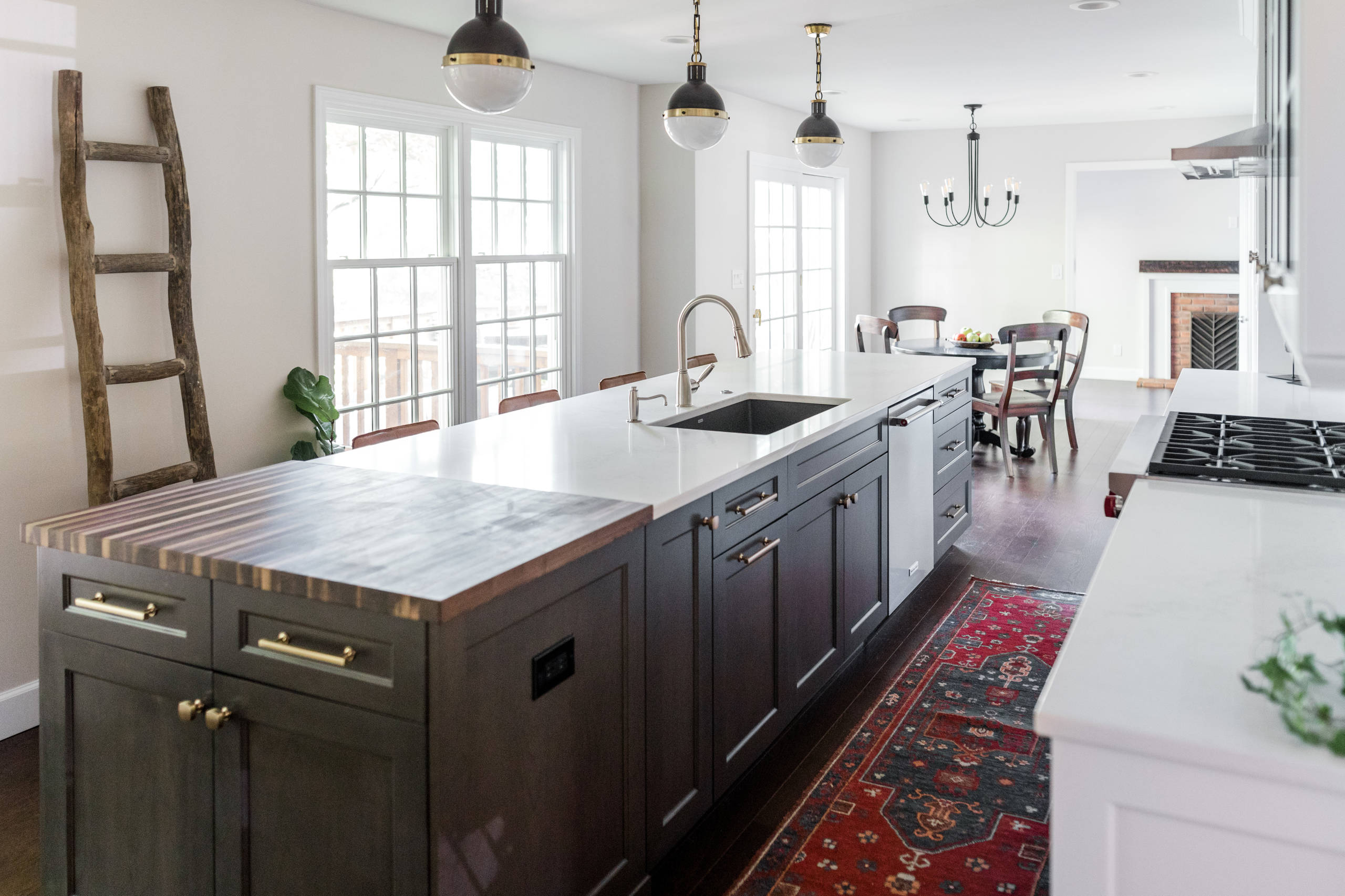 Example of a large transitional l-shaped medium tone wood floor and brown floor eat-in kitchen design in Detroit with an undermount sink, shaker cabinets, medium tone wood cabinets, wood countertops,