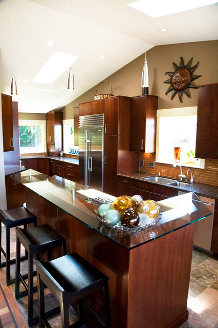 Large minimalist u-shaped slate floor open concept kitchen photo in Seattle with a double-bowl sink, flat-panel cabinets, dark wood cabinets, granite countertops, brown backsplash, glass tile backsplash, stainless steel appliances and an island
