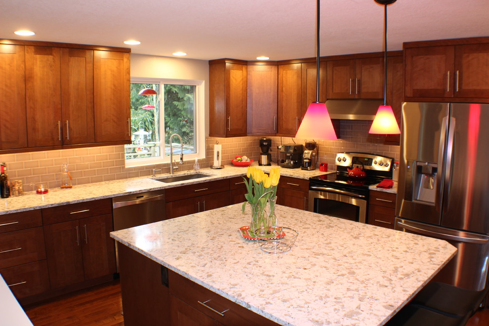 Example of a large trendy u-shaped medium tone wood floor eat-in kitchen design in Seattle with a single-bowl sink, shaker cabinets, medium tone wood cabinets, quartz countertops, beige backsplash, glass tile backsplash, stainless steel appliances and an island