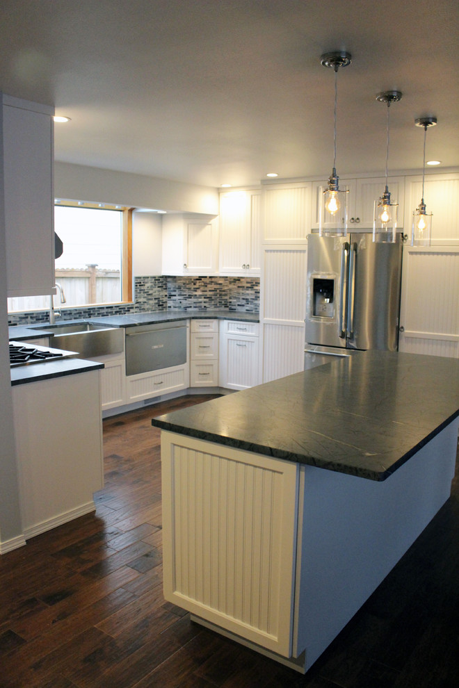 Example of a large arts and crafts u-shaped dark wood floor kitchen design in Seattle with a farmhouse sink, white cabinets, soapstone countertops, stainless steel appliances, an island, blue backsplash and mosaic tile backsplash