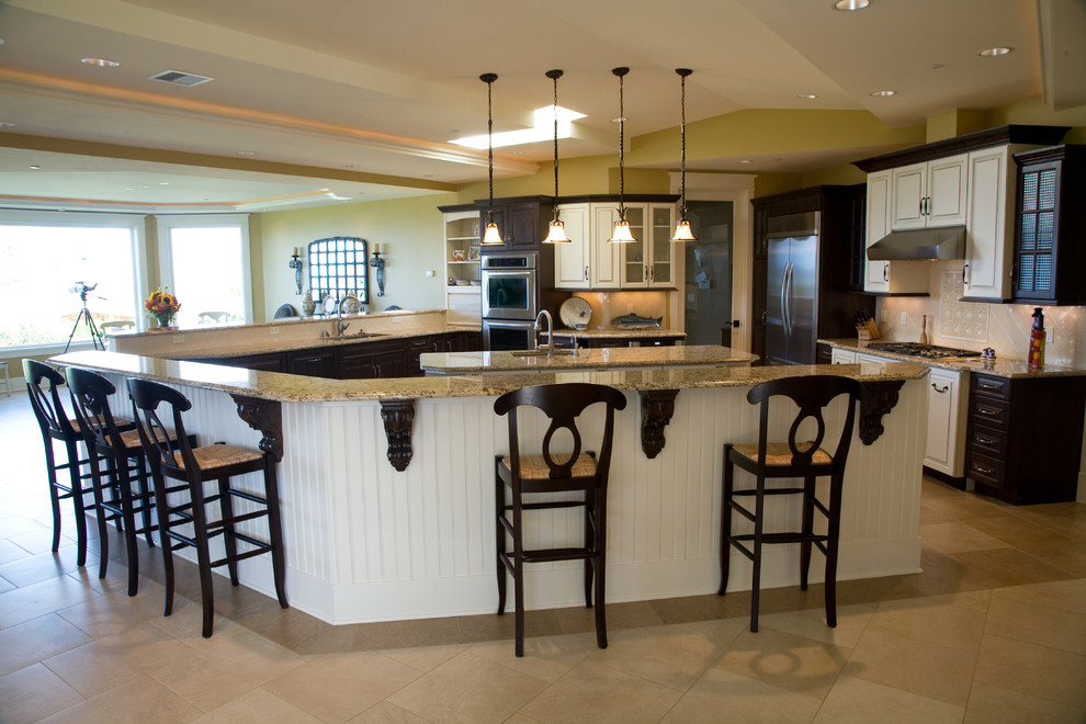 Huge elegant l-shaped travertine floor open concept kitchen photo in Seattle with a single-bowl sink, raised-panel cabinets, white cabinets, granite countertops, white backsplash, ceramic backsplash, stainless steel appliances and two islands