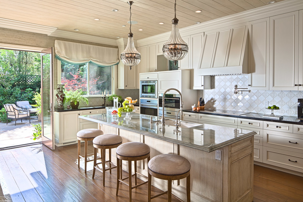 Example of a classic l-shaped medium tone wood floor and brown floor kitchen design in Los Angeles with an undermount sink, recessed-panel cabinets, beige cabinets, white backsplash, stainless steel appliances, an island and black countertops