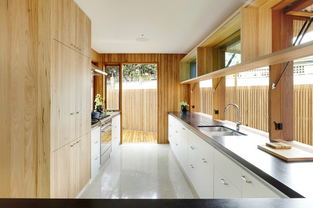 This is an example of a contemporary galley kitchen in Melbourne with flat-panel cabinets and white cabinets.
