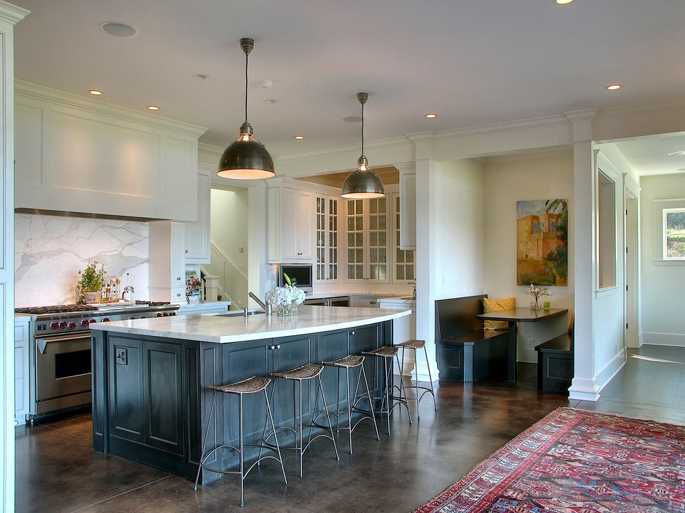 Example of a classic brown floor kitchen design in Seattle with glass-front cabinets and stainless steel appliances