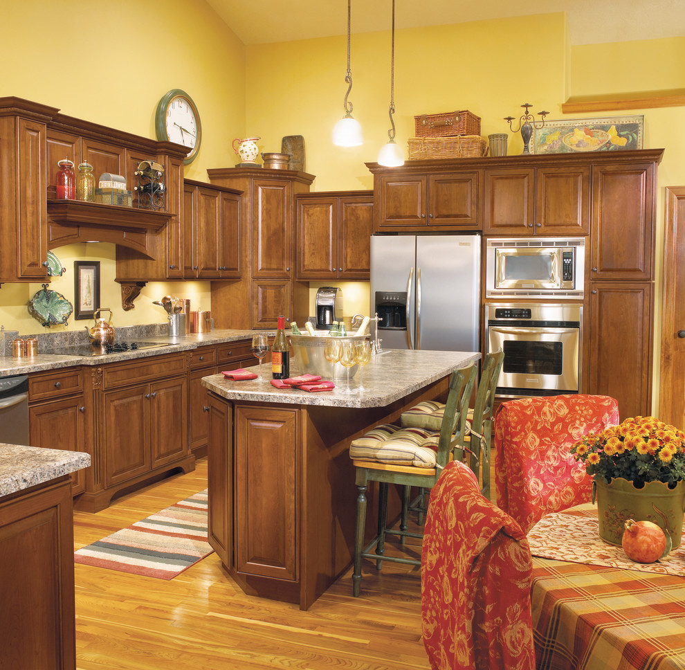 Eat-in kitchen - large traditional light wood floor eat-in kitchen idea in Other with raised-panel cabinets, medium tone wood cabinets, stainless steel appliances, an island and a drop-in sink
