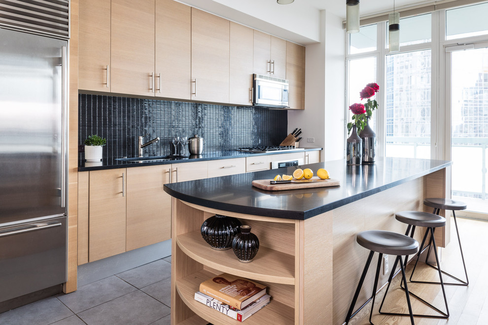 Trendy single-wall gray floor kitchen photo in New York with an undermount sink, flat-panel cabinets, light wood cabinets, black backsplash, stainless steel appliances, an island and black countertops