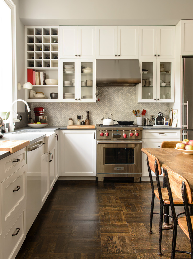 Example of a classic l-shaped dark wood floor and brown floor eat-in kitchen design in New York with white cabinets, a farmhouse sink, shaker cabinets, gray backsplash, stainless steel appliances and no island