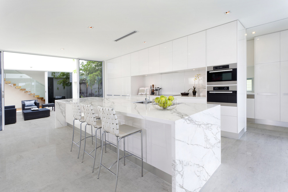 Inspiration for a contemporary galley kitchen remodel in Miami with flat-panel cabinets, white cabinets, white backsplash, stainless steel appliances, an island and a double-bowl sink