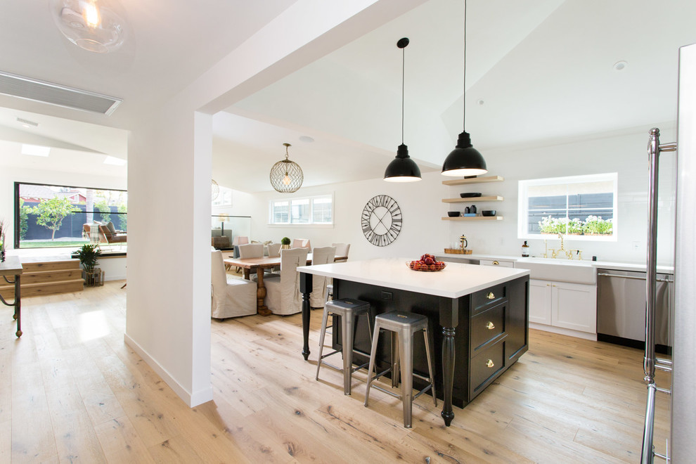 Example of a cottage light wood floor open concept kitchen design in Los Angeles with a farmhouse sink, shaker cabinets, white cabinets, quartzite countertops, stainless steel appliances and an island