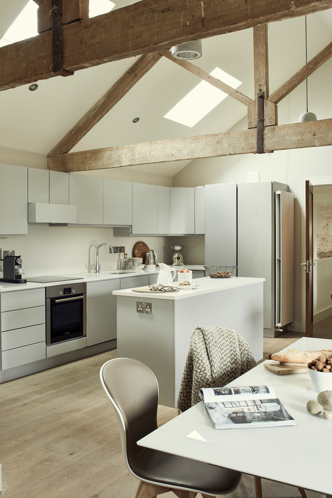 Example of an urban single-wall light wood floor and beige floor eat-in kitchen design in Other with flat-panel cabinets, gray cabinets, white backsplash, stainless steel appliances and an island