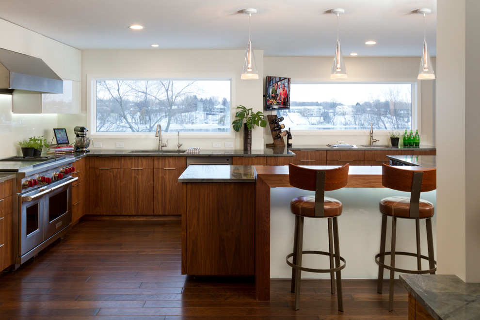 Large trendy l-shaped dark wood floor eat-in kitchen photo in Minneapolis with an undermount sink, flat-panel cabinets, medium tone wood cabinets, granite countertops, white backsplash, glass sheet backsplash, stainless steel appliances and an island