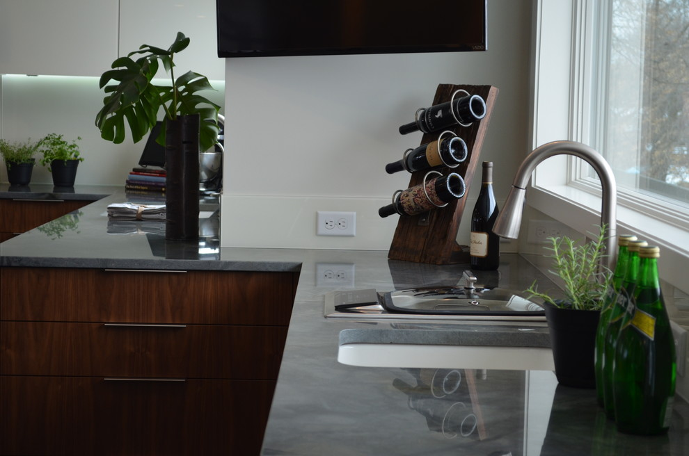 Eat-in kitchen - large contemporary l-shaped dark wood floor eat-in kitchen idea in Minneapolis with an undermount sink, glass-front cabinets, medium tone wood cabinets, granite countertops, white backsplash, glass sheet backsplash, stainless steel appliances and an island