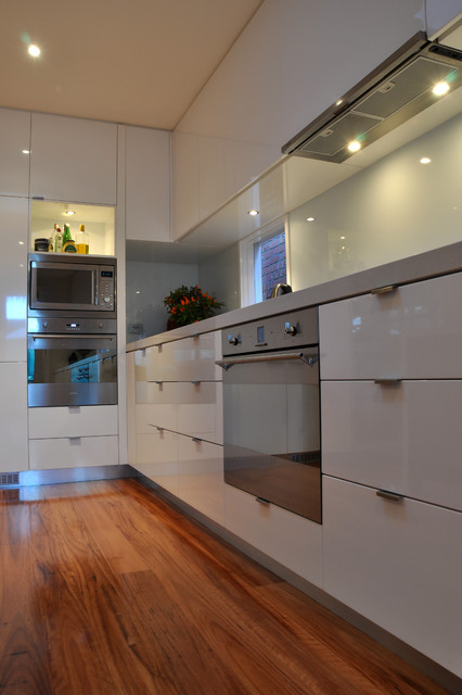 Open concept kitchen - mid-sized modern l-shaped light wood floor open concept kitchen idea in Geelong with an undermount sink, flat-panel cabinets, white cabinets, quartz countertops, white backsplash, glass sheet backsplash, stainless steel appliances and an island