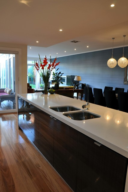 Mid-sized minimalist l-shaped light wood floor open concept kitchen photo in Geelong with an undermount sink, flat-panel cabinets, white cabinets, quartz countertops, white backsplash, glass sheet backsplash, stainless steel appliances and an island