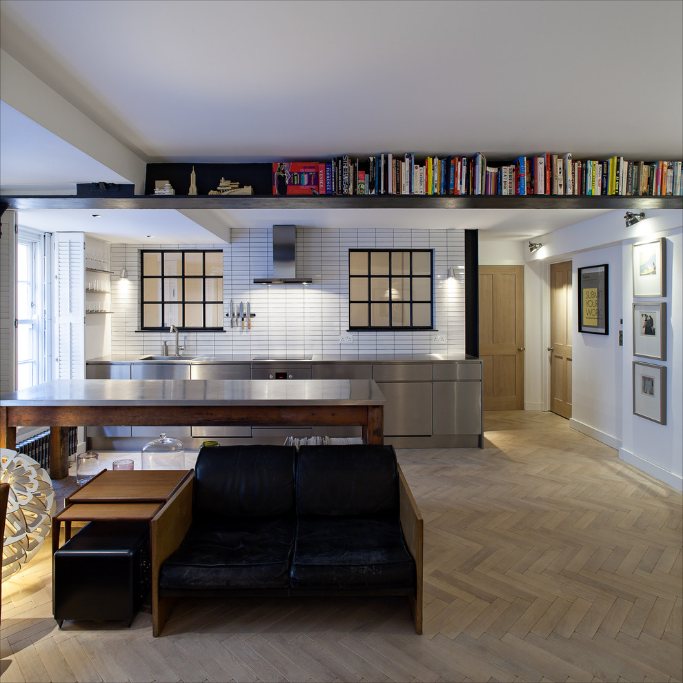 Example of an urban single-wall kitchen design in London with stainless steel countertops
