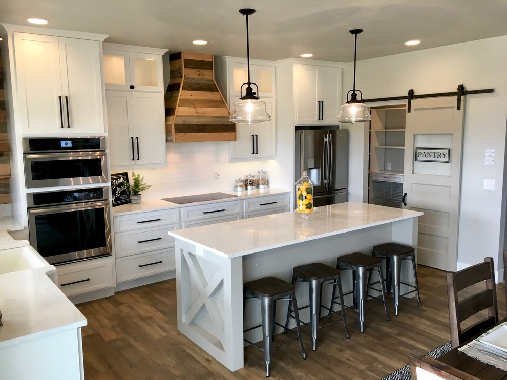 Inspiration for a mid-sized farmhouse u-shaped vinyl floor and brown floor eat-in kitchen remodel in Other with a farmhouse sink, shaker cabinets, white cabinets, marble countertops, white backsplash, subway tile backsplash, stainless steel appliances and an island