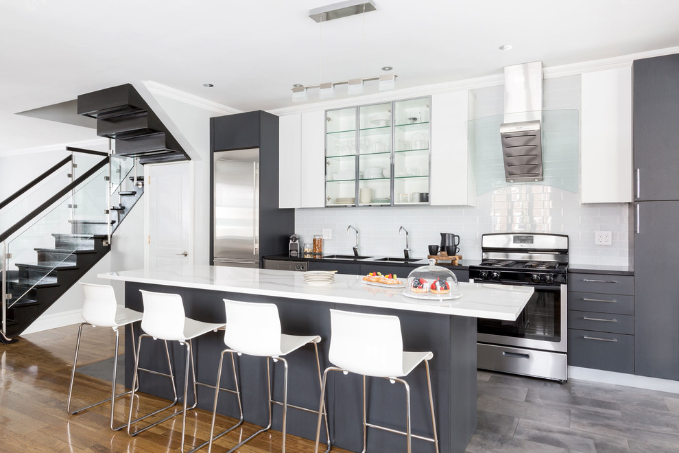 Example of a trendy gray floor open concept kitchen design in New York with an island, a double-bowl sink, glass-front cabinets, stainless steel cabinets, white backsplash, subway tile backsplash, stainless steel appliances and black countertops