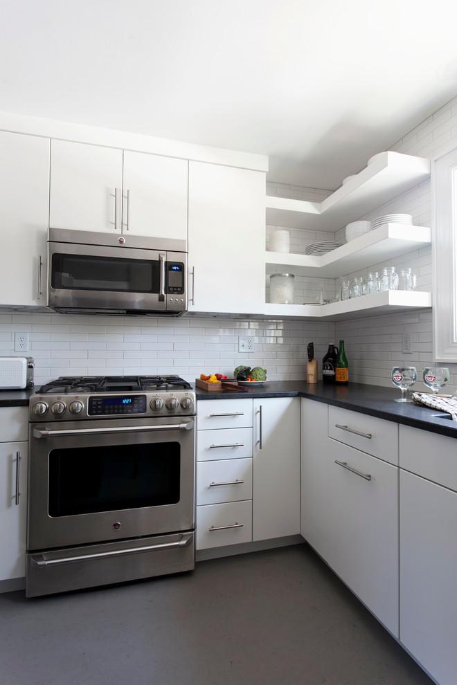 Enclosed kitchen - small modern u-shaped linoleum floor enclosed kitchen idea in Bridgeport with an undermount sink, white cabinets, white backsplash, ceramic backsplash, stainless steel appliances and an island